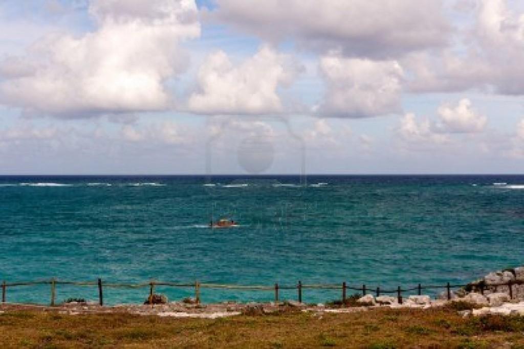 05 13087968-pequeno-barco-rojo-pasa-throgh-la-vista-desde-un-acantilado-sobre-el-mar-turquesa-de-tulum-quintana-